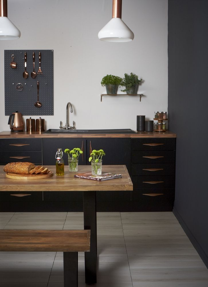 Black kitchen, grey and black kitchen. The introduction of wood, with the table and worktop, adds depth, texture and character, whilst the beautifully reflective, and fashionable, copper utensils create a little lustre.