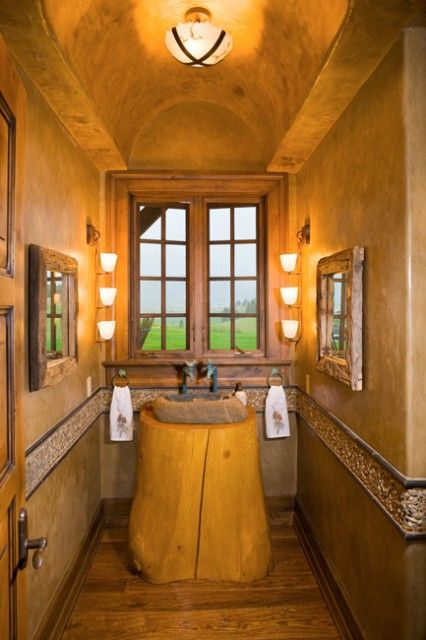 """Rustic nature… this powder room features an arched barrel ceiling and walls faux painted to have a """"leather"""" look, rustic oak floors, an inlaid pebble stone chair rail, and a natural stone sink with a tree stump vanity.  (via Bridger Canyon Residence - eclectic - powder room - other metros - by Locati Architects)"""