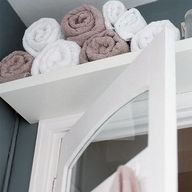 Take advantage of the wasted space above the door in a bathroom* CLEVER!!!  For the downstairs loo!