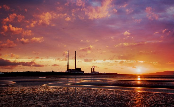 A photograph by photographer Niall O Cleirigh of Sunrise at the strand showing the Red and white chimneys silhouetted by the bright and colou... www.essentia.ie