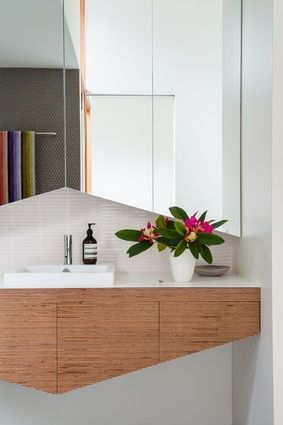 The bathroom joinery is an abstraction of a pitched roof.