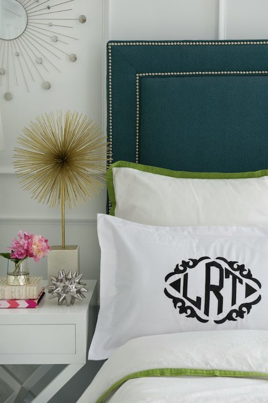 Upholstered headboard with nailhead detail, monogrammed pillows