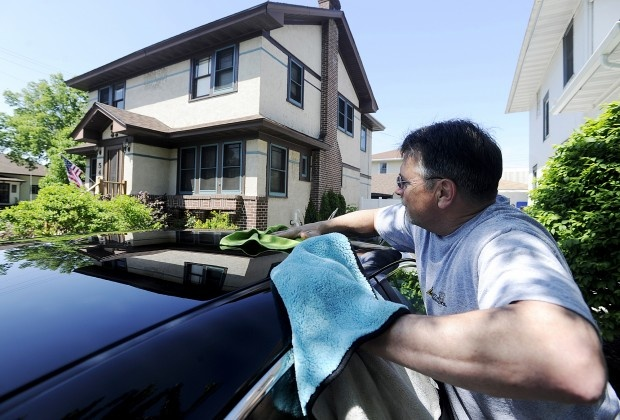 "Dan Miller, of Winona, waxes his wife's car on Sunday, May 13, 2012, in Winona. Miller said he was, ""putting an aerospace shine on it."" (Joe Ahlquist/Winona Daily News)"