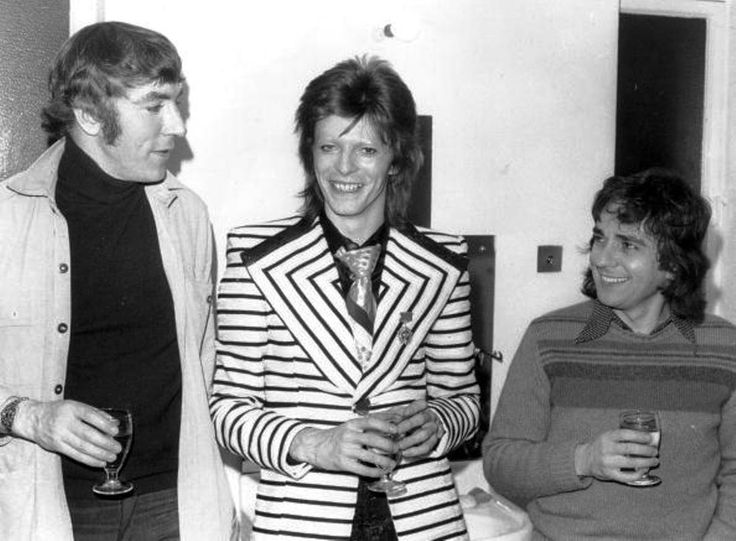 David Bowie, sporting a stripy jacket with wide lapels, visits comedy duo Peter Cook (1937 - 1995), and Dudley Moore (1935 - 2002) backstage at the Cambridge Theatre in London, following the pair's show 'Behind The Fridge'. 9th May 1973