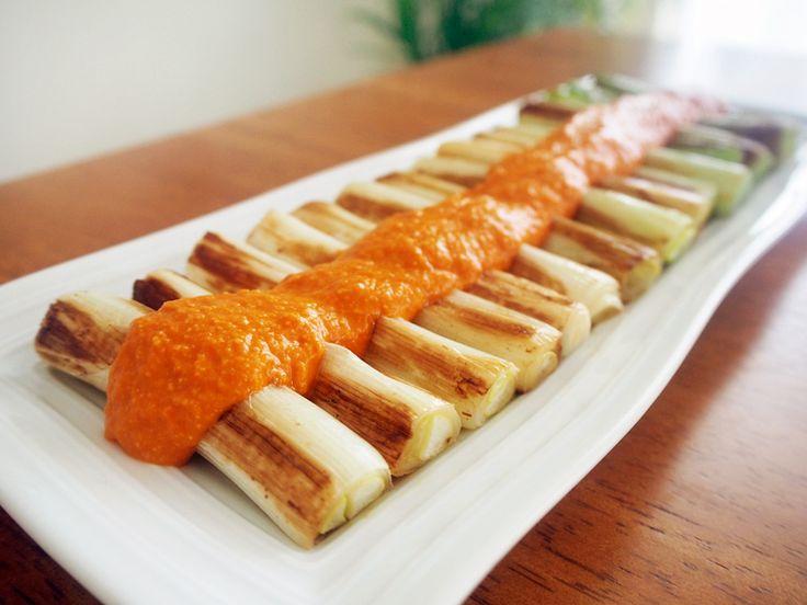 焼きネギと野菜ソースのカルソッツ風2~4人分 長ネギ2本 パプリカ1/2個 タマネギ1/2個 B カットトマト50g B アーモンドスライス10g B パプリカパウダー小さじ1/2 B 塩小さじ1/4 オリーブオイル大さじ1 ロメスコソースを作る。 タマネギ・パプリカは2cm角にカットし、オリーブオイルで炒める。 Bを加え弱火で15分煮、塩コショウで調味。ブレンダーで攪拌する。 長ネギは食べやすい大きさにカット。 オリーブオイルを熱してこんがり焼き色がつくまでソテーする。 ネギを並べて塩コショウ少々をふり、ソースをかける。 ★カルソッツ(Calcots)とは、真っ黒に網焼きしたネギの外側をむき、内側の柔らかい部分にソースをつけていただくお料理。食器は使わず、手を真っ黒にしながら豪快に食べる、スペイン・カタルーニャ地方の風物詩。 ★今回は手軽に食べるカルソッツ風というイメージで、フライパン焼きにアレンジしました。 ★ロメスコソースはグリルポークや白身魚のソテー、卵料理、ポテトやパンにつけても美味しいですよ。