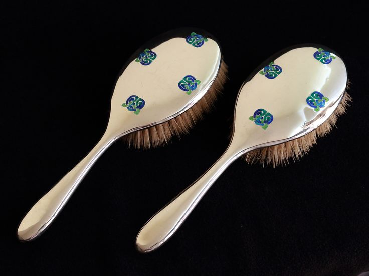 A pair of Liberty & Co silver and enamel hairbrushes designed by Archibald Knox, with Celtic knot panels enamelled in vibrant shades of blue and green   Hallmarked Birmingham 1916 along with  with L&Co makers mark and model number 5692