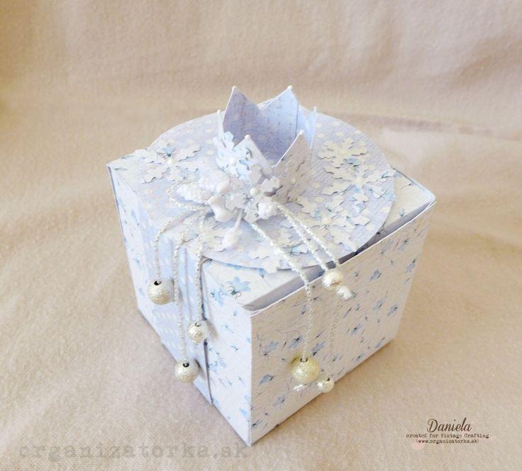 Dnes som si pre vás pripravila návod na vytvorenie darčekovej krabičky: Krabičku som vytvorila z papiera zo zimnej kolekcie Frosty Morning od UHK Gallery. Každá strana má 7 cm, na fotografii vidíte šablónu s mierami, ktorú som si namerala a vyrezala: Menšie, dvojcentimetrové časti, som si jemne zostrihla do šikma: Základ krabičky som podľa čiar prehla smerom do vnútra: Na dvojcentimetrové časti som nalepila obojstrannú lepiacu pásku a krabičku som zlepila: Nakoniec som voľne zatvorila vrchnú…
