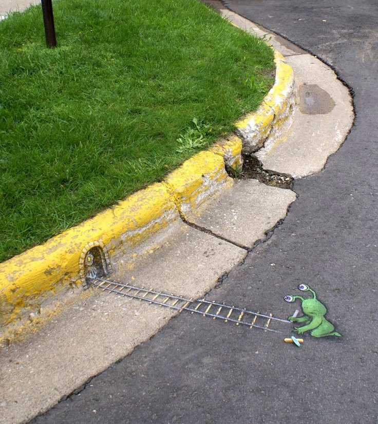 David Zinn street art. Green alien (Sluggo) drawing train tracks on the street curb