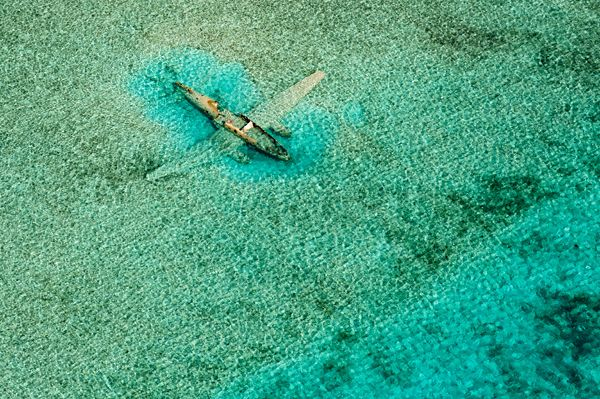 An abandoned plane stands out in shallow water east of the airport on Norman's Cay in the Bahamas.