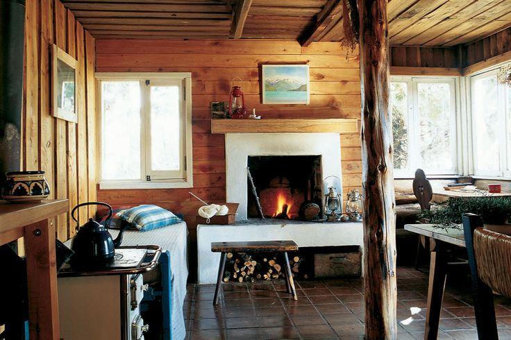 Living comedor de una cabaña luminosa con paredes y techo de madera. Chimenea a leña, muebles estilo campo y piso de cerámica marrón.
