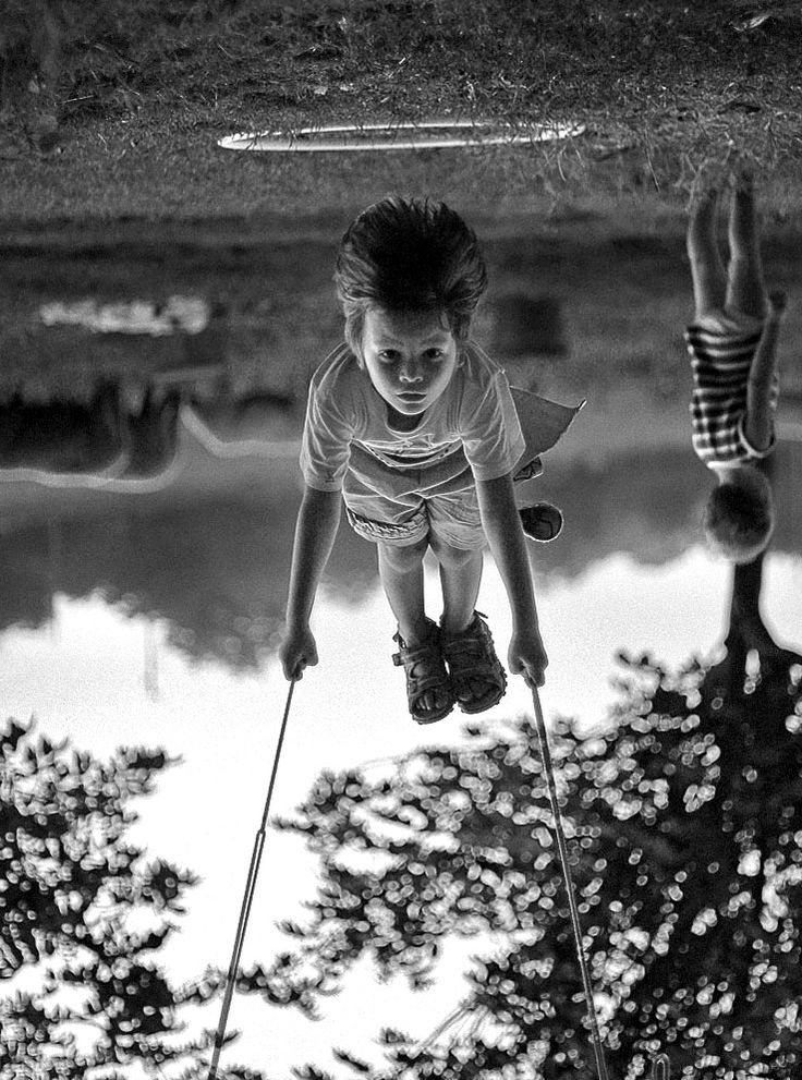 Awesome black white photograph of children playing on a swing set upside down