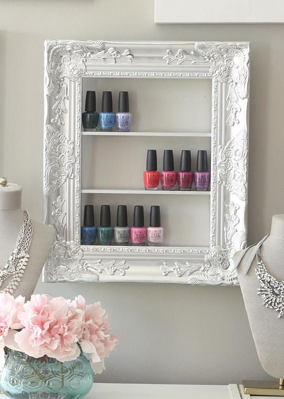 "This is the perfect way to display your nail polish, show off the beautiful bottles and colors in the perfect frame. Although designed to be a display case, this is also a perfect storage item, pick up a few coordinating frames and create a gallery wall in your home or salon!  This frame is handcrafted- assembled and painted by hand. This is an upcycled frame, (as shown) 15 X 18, an opening measuring 10 X 13.5and sits approximately 2 ¼ "" off the wall, including the frame. Three shelves, each…"
