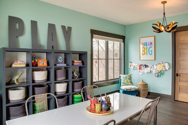 Contemporary playroom features walls painted green fitted with a dark gray framed window next to ...