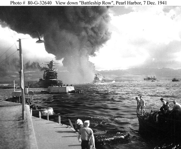 "View looking down ""Battleship Row"" from Ford Island Naval Air Station, shortly after the Japanese torpedo plane attack. USS California is at left, listing to port after receiving two torpedo hits."