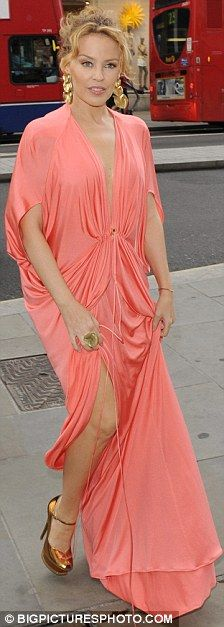 Glamour: Kylie Minogue shows off her figure in a revealing, draped coral Bodyamr dress as she arrives at the Tous jewellery party last night...