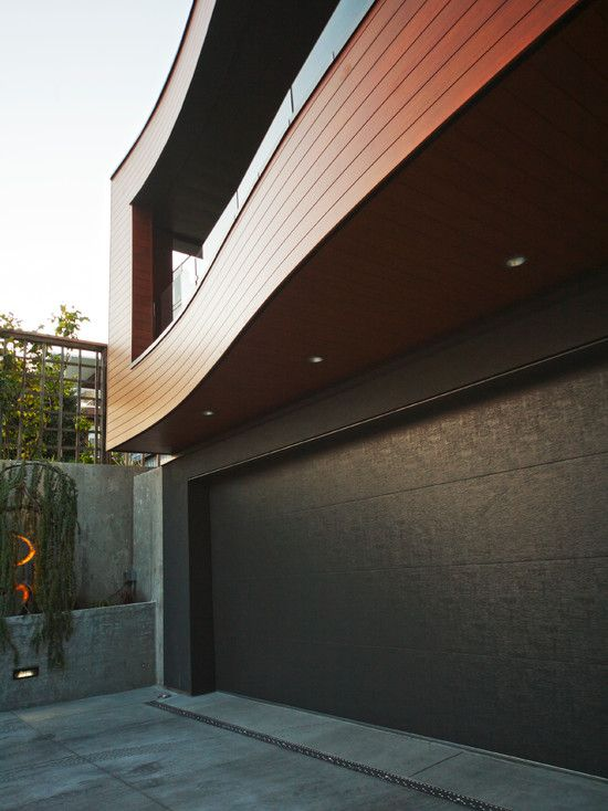 Exciting Modern Garage Door for Your Home: Modern Exterior Design With Black Modern Garage Door With Brown Bedboard Wall Accent Also Modern Balcony Design And Gray Concrete Floor Material ~ vettelicious.com Garage Ideas Inspiration