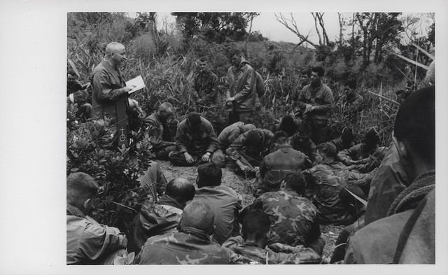 "Easter Services, 1969  ""Oklahoma Easter: Navy Chaplain (Lieutenant Commander) R. W. Harper (Oceanside, California) conducts Easter services for the 7th Marine Regiment Leathernecks during Operation Oklahoma Hills, a multi-battalion operation west-southwest of Da Nang. This Easter was a short break between combat assaults upon Charlie and Worth Ridges, long known enemy supply routes."""