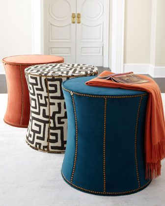 "Nailhead trim accents these drum-shaped ottomans that work well as both side tables or footrests.  Peacock-blue ottoman is covered in 100% polyester.  White patterned fabric is covered in cotton/rayon; outdoor safe.  Rust-colored ottoman is covered in pure cotton.  Select color when ordering.  22""Dia. x 23""T.  Made in the USA."