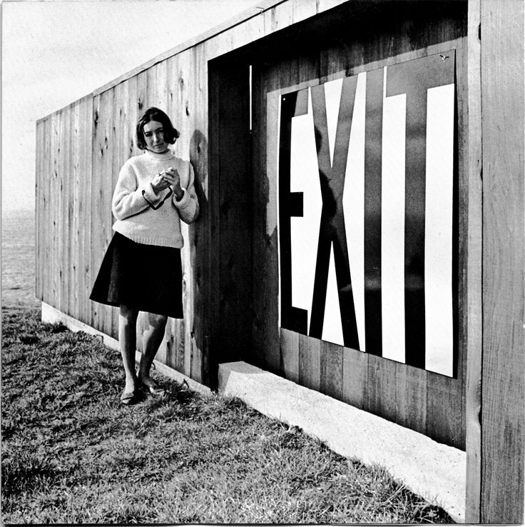 Barbara Stauffacher Solomon beside an enamel exit sign at Lawrence Halprin's house at The Sea Ranch.    The Big Bold World of Barbara Stauffacher Solomon - Creative Review