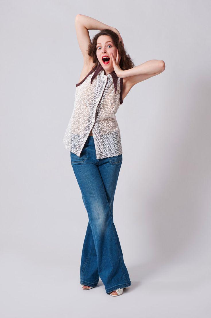 Witte kanten blouse afgezet met paarse breisels, afgezet aan kraag en armsgaten.