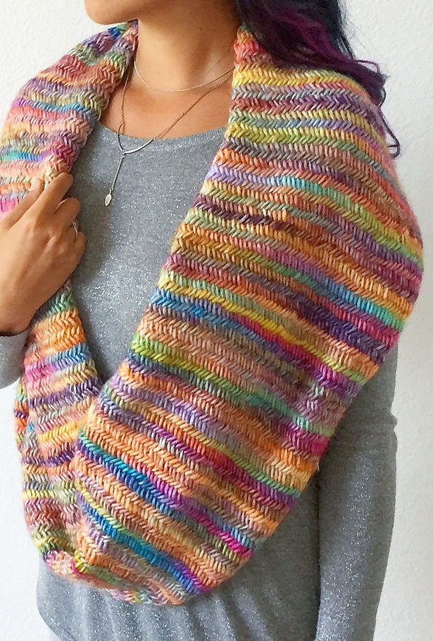 Free Knitting Pattern for 2 Row Repeat Misty Rainbow Infinity Scarf - A two row repeat herringbone stitch creates a colorful cowl with beautiful texture. Photo tutorial of the herringbone stitch included. Designed by Life Is Cozy to showcase multi-color yarn but also creates a beautiful solid color scarf.