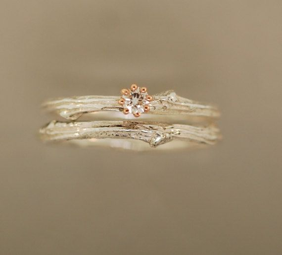 Dainty Twig Ring Set This ring features a forever one moissanite from Charles and Colvard set with a delicate basket setting that is 14 karat solid rose gold. The twig is sterling silver. The moissanite is three mm. The band is 1.65 mm to 2.7 mm. The coordinating band is a sterling