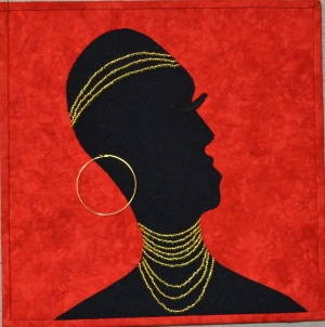 My first 12x12 challenge.  African lady with beads.  Machine quilting words on black are from within a woman.  Words on red are negative outside influences