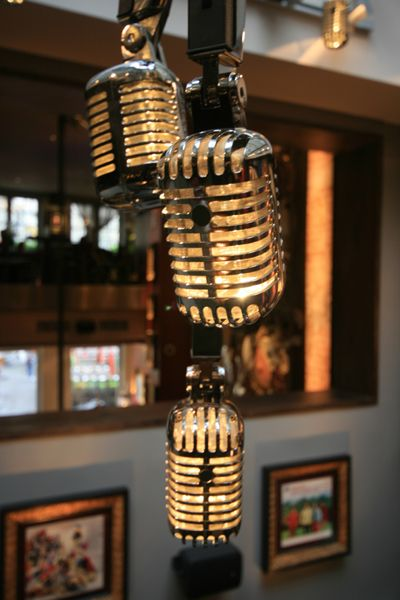 The microphone chandelier built to a Fuse design by Technical Arts, it uses angle poise lamp frames and microphones to create a unique light fitting which is flown below the existing roof light above the small stage. Matching microphone pendant lights are hung over the bar counter and in the entrance lobby.