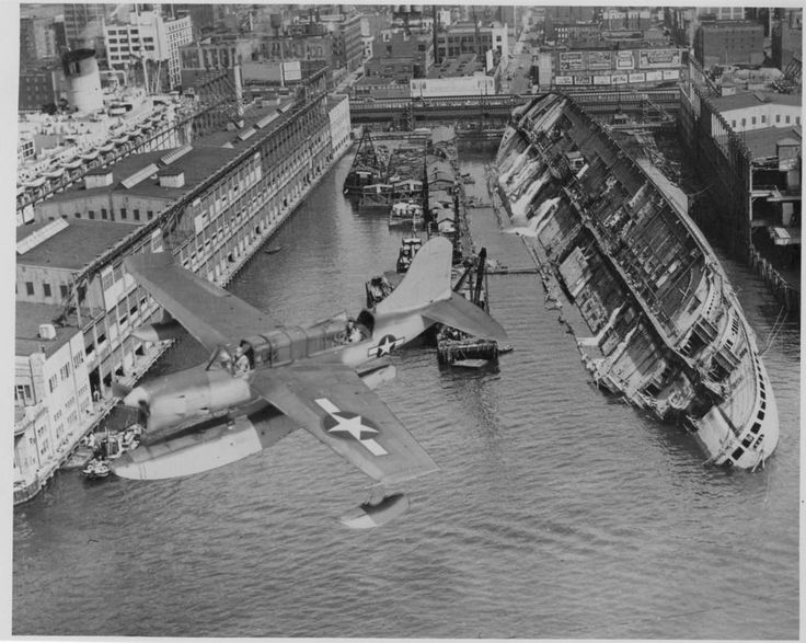 close-to-the-knives:  adventures-of-the-blackgang:   SS Normandie sunk at the Pier  SS Normandie was an ocean liner built in Saint-Nazaire, France, for the French Line Compagnie Générale Transatlantique. She entered service in 1935 as the largest and fastest passenger ship afloat. During World War II, Normandie was seized by US authorities at New York and renamed USS Lafayette. On 9 February, 1942, the liner caught fire while being converted to a troopship, capsized onto her port side and…