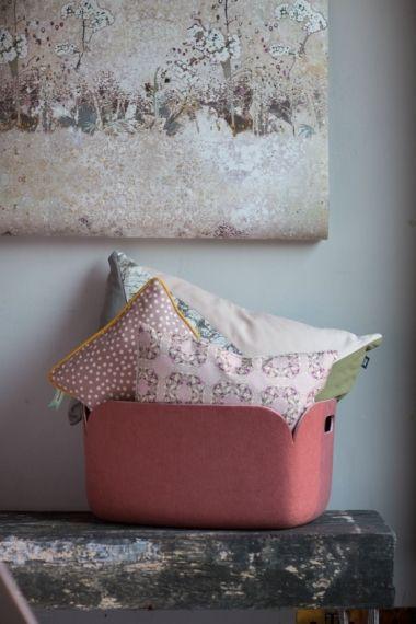 Meadow Sand wallpaper, Louise Body; rose felt basket, Muuto; triangle cushion and blush polka-dot cushion, both Ferm Living. Pink rose cushion, Abigail Ryan.