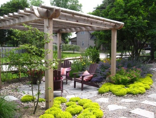 Arbor, stones, xeriscaping plants... great creation of a place within a space.