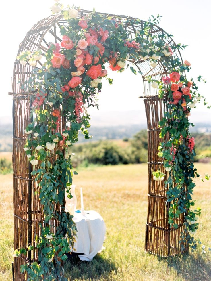 Ceremony Arch with coral and peach flowers of peonies and garden roses with trailing foliages from Sunny and Sarah's Central Coast wedding at Presquil'e winery. See more here: http://noonansdesigns.com/portfolio/