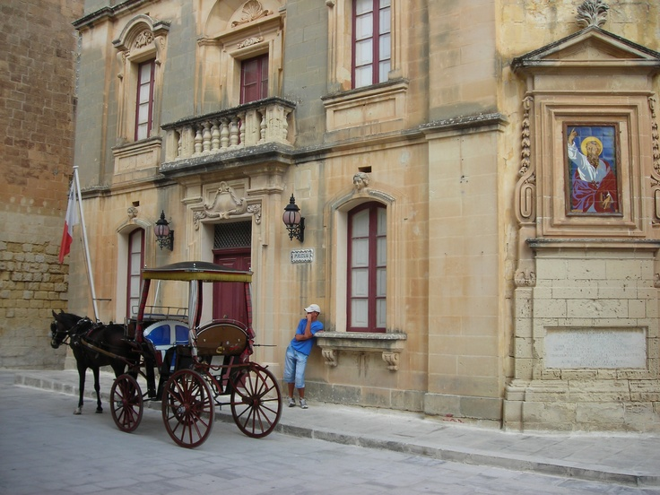 Horse Cart known as a Karrozzin is parked outside the police station in Medina, Malta