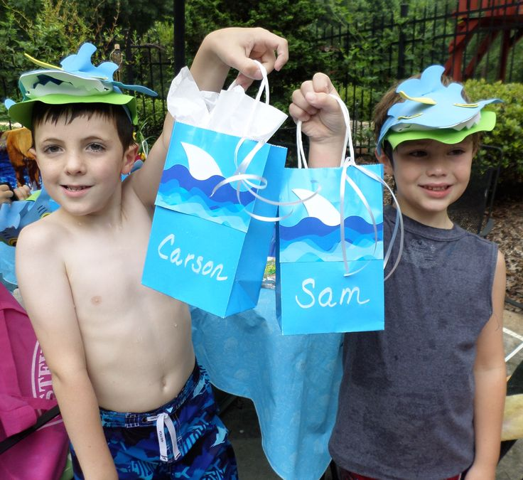 """A shark birthday party turns guests into """"not too scary sharks"""" with foam visors who are excited about what shark party favors are inside the home-made party bags."""