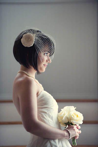 Une coiffure de mariage pour cheveux courts avec voilette et fleur