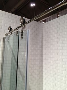 Incredible shower with beveled subway tile surround and sliding barn glass shower door.