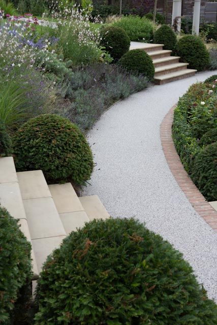curving path soften by box balls, sandstone large slap steps leading down to, grey path edged in red brick