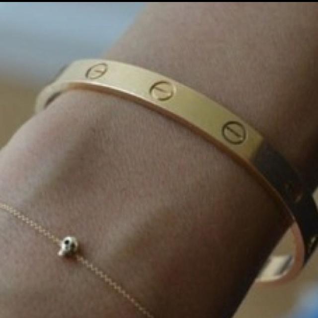 cartier love bracelet. skull charm. gold jewelry.