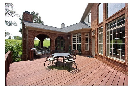 Graceful Brick Arches Lead To A Covered Patio And