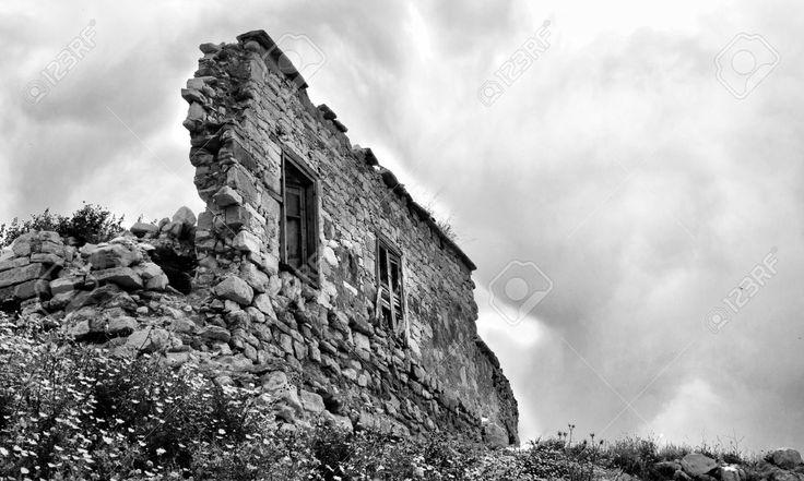 Pared ruinas permanente contra un cielo nublado.