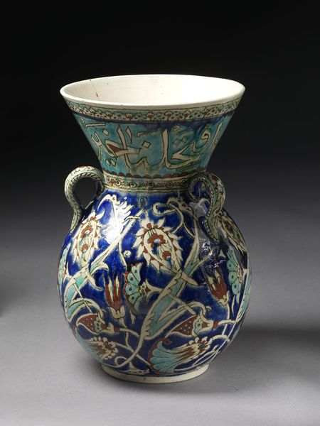 Mosque lamp   Made in Kütahya, Turkey, ca. 1875-1892   Materials: fritware, polychrome painted, glazed   Mosque lamp of fritware, painted with floral designs in colours on a dark blue ground; round the neck runs an inscription on a turquoise ground. The lamp has three loops for suspension   VA Museum, London