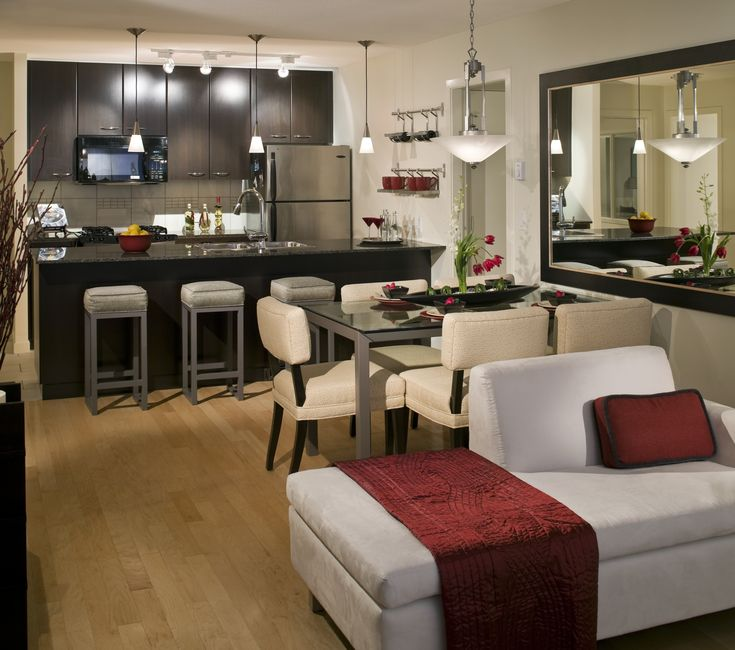 Small, open layout with a stainless steel appliances, granite countertops, neutral color walls, ceramic tile and dark cabinets to offset the white couch and leather chairs. This space shows how elegant and radiant you can make a small space look with the right design.