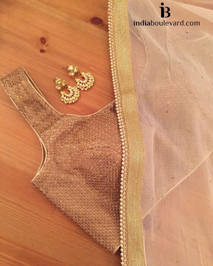 Gold/copper sequin blouse paired with a beige saree and gold border with pearl trimmings.