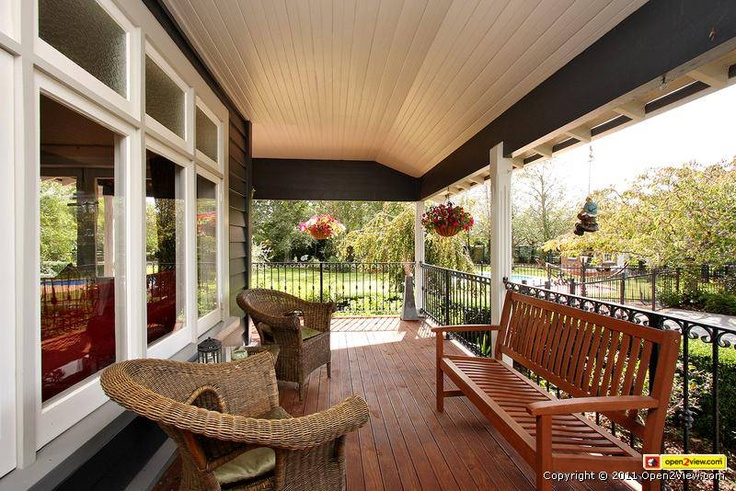 Pretty porch. Black weatherboard and white trim windows.