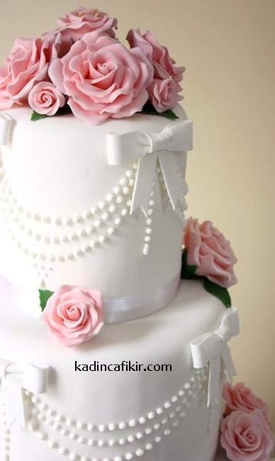 Düğün pastalarına örnek olarak beyaz fiyonklu, boncuklu, pembe güllü katlı beyaz düğün pastası modeli | Kadınca Fikir
