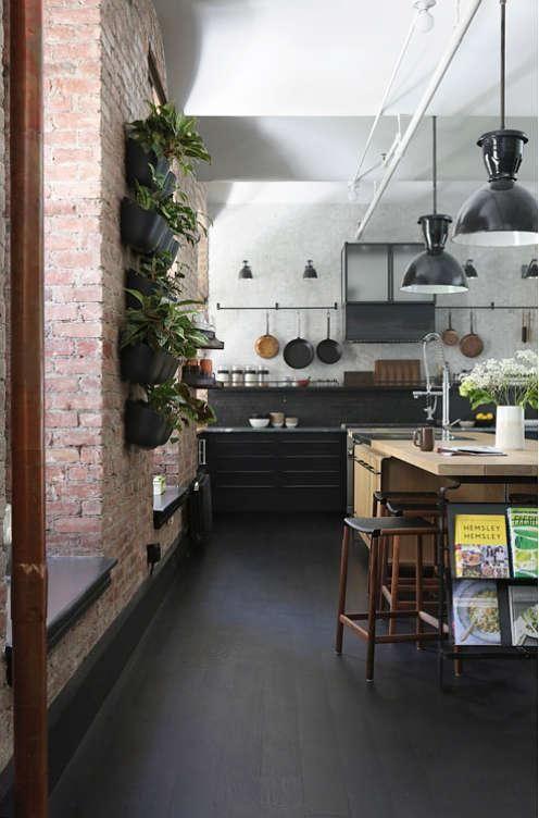Die Küche verfügt über schwarze Schränke und eine warme, farbige, lange Kücheninsel, die mit großen Pendelleuchten definiert ist
