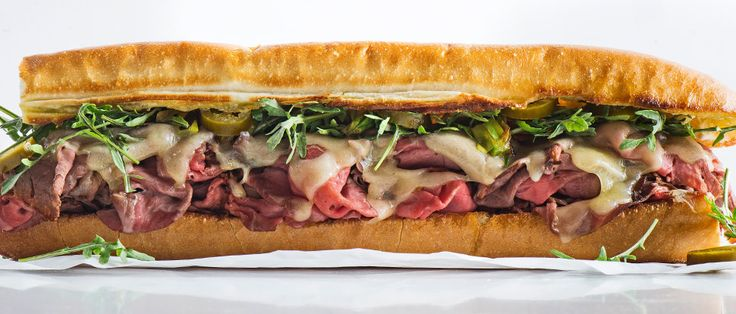 This sandwich, served warm, is stacked high with roast beef and melty Swiss cheese. Charred scallions add even more savory notes, while pickled jalapeños add a jolt to every bite.