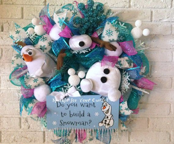 Olaf Frozen Christmas Wreath, Do You Want To Build a Snowman? The Disney Frozen inspired wreaths are done and I am very happy with them. I worked very hard to find a color palette that worked with the blues, silver and white that are in the movie. These wreaths were challenging for me, but it was well worth it. I love the textures, colors and the snowballs in the ribbon. They sparkle and they are squishy. Gotta love the Mickey Head Snowballs! I painted them white and sprayed silver glitter…