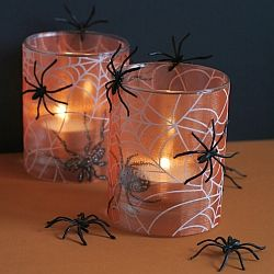 Printed spider web organza adhered to glass adds instant Halloween spookiness to a room. Fake spiders add extra fright to the decoration.