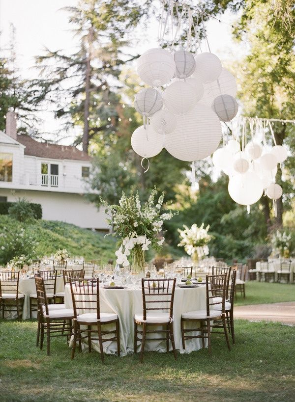 Lovely outdoor reception tablescape featuring Short & Tall Centerpieces with floral arrangements and hanging paper lanterns #FlourishingFlowerTowers #VasesAndVessels